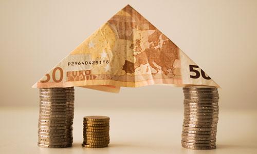 Ein Haus aus Geldscheinen und Münzen
