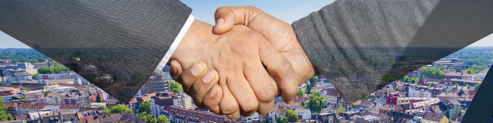 Zwei Geschäftspartner geben sich die Hände vor einer Ansicht der Stadt Bochum